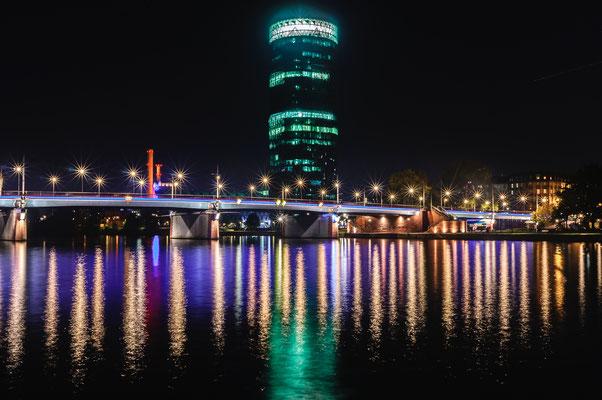 Westhafen-Tower in der Nacht mit Blick auf die Friedensbrücke eine Autobrücke über den Fluss Main in Frankfurt