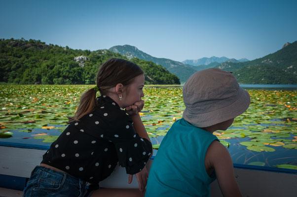 Zwei Kinder beobachten still den Skadarsee vom Boot aus