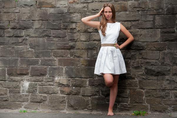 Junge Frau im weißen Kleid an einer grauen Steinwand aus Naturstein