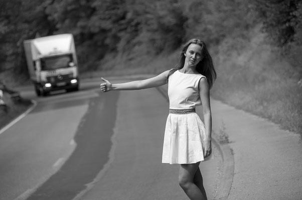 Eine junge wunderschöne hübsche russische Frau sucht auf der Straße eine Mitfahrgelegenheit mit einem Auto