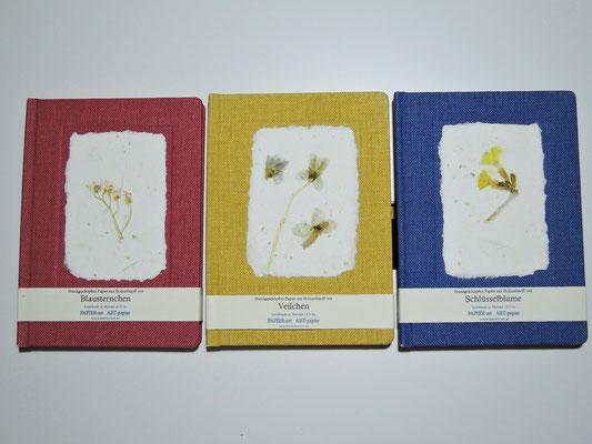 Handgebundene Bücher  mit Leineneinband und hangeschöpftem Papier mit Blüten