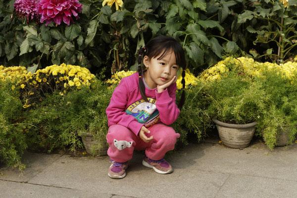 Kleines Mädchen, das für Foto posiert