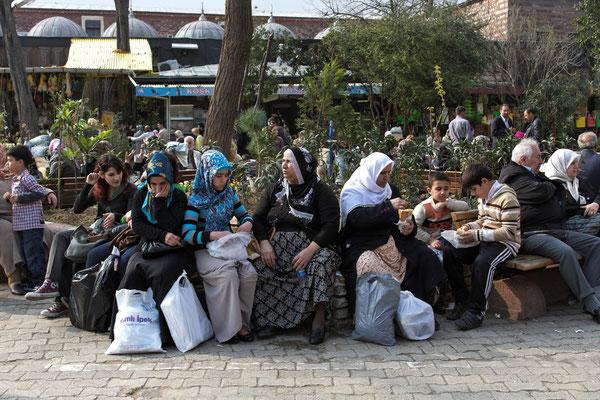 Frauen warten mit ihren Einkäufen am Verkehrsknotenpunkt Eminönü