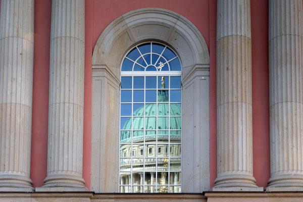 Kuppel der Nikolaikirche spiegelt sich im Fenster des Stadtschlosses