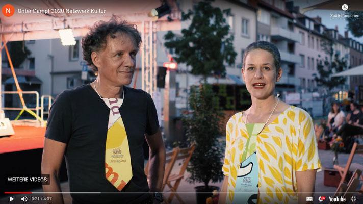 """""""Unter Dampf"""" bei """"Urban Places Reloaded"""" auf dem Hildesheimer Angoulêmeplatz: Jürgen Zinke und Sabine Zimmermann vom Netzwerk Kultur & Heimat. (Screenshot des Filmtrailers)"""