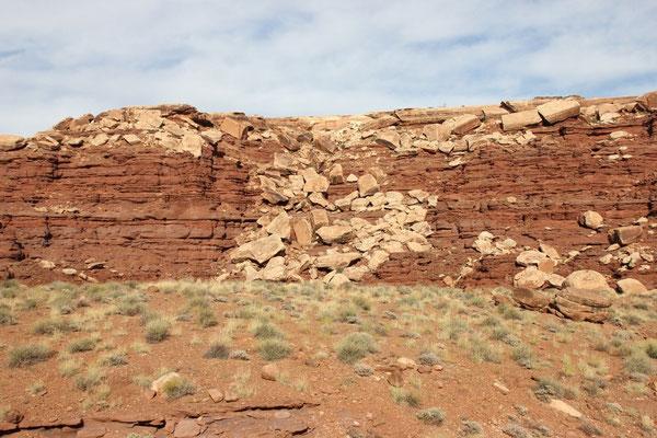 Die weisse Schicht bricht langsam ab, da das rote Gestein darunter erodiert.