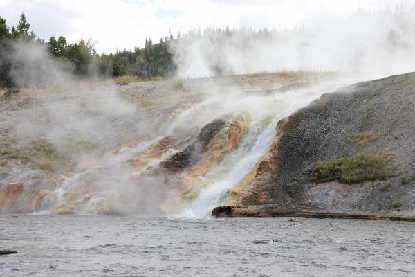 Der heisse Wasserfall ergoss sich in den kalten Fluss.