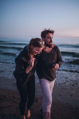 Zukünftiges Brautpaar läuft den Strand entlang und genießen die letzten Sonnenstrahlen und die Seeluft
