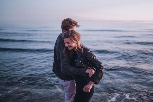 Verlobung am spanischen Meer. Brautpaar genießt die Zweisamkeit während des Sonnenuntergangs