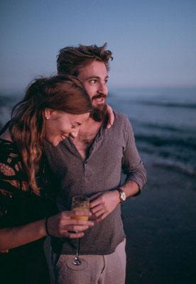 Frau lehnt sich an die Brust des Mannes an, während das Paar einen Strandspaziergang macht