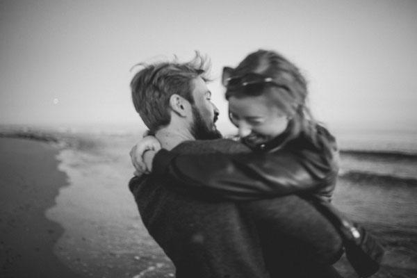 Authentisches Paar lachen und haben Spaß an einem warmen Sommertag am Strand
