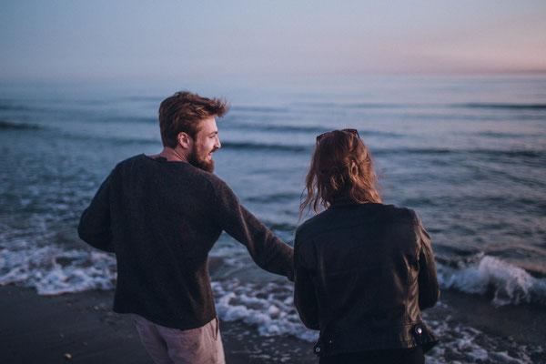 Junges Pärchen läuft lachend am Strand entlang und genießt den Sonnenuntergang