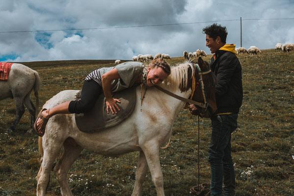 Plötzlich tauchte eine Schafherde am Horizont auf. Umringt wurde sie von mehreren Reitern. Als die Hirten uns sahen, kamen sie zur Straße galoppiert. Sie fragten Tine, ob sie reiten möchte. Der Aufstieg gestaltete sich als schwierig! :)