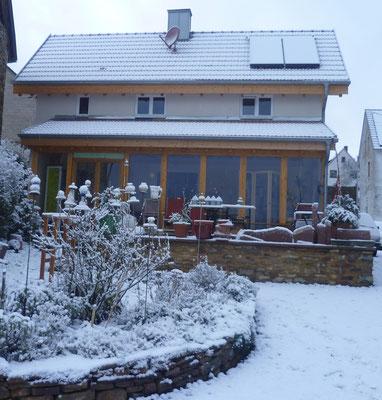 Blick auf unser Ferienhaus mit Wintergarten und Terrasse vom Garten aus