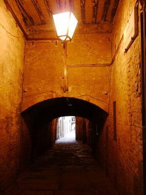 dunkle, überdachte Gänge unter Häusern her