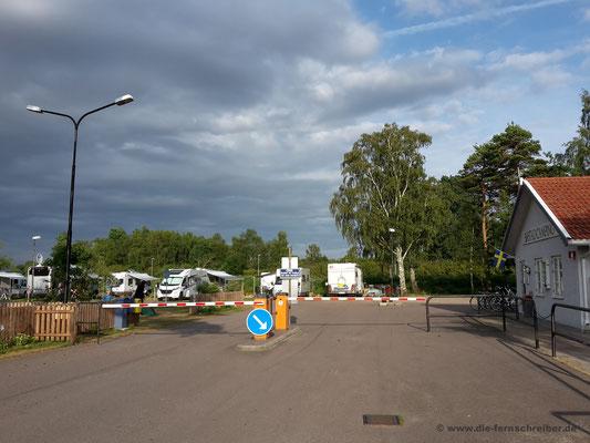 Campingplatzeinfahrt mit Sicht nach außen auf die Stellplätze vor der Schranke