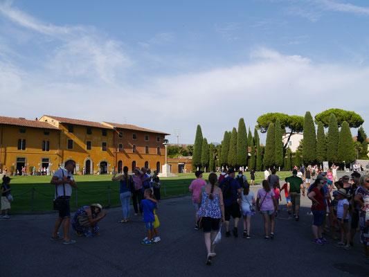 Ende einer Warteschlange zur Turmbesichtigung, im Hintergrund die Touristeninformation  in schönen toskanischen Häusern