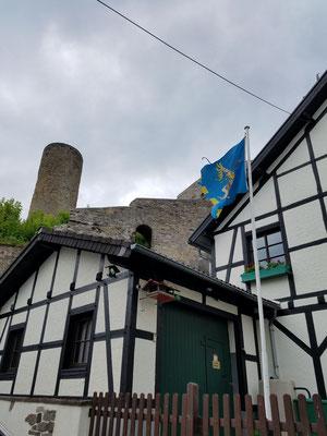 Unten Fachwerk mit Ritterflagge, oben Burgruine