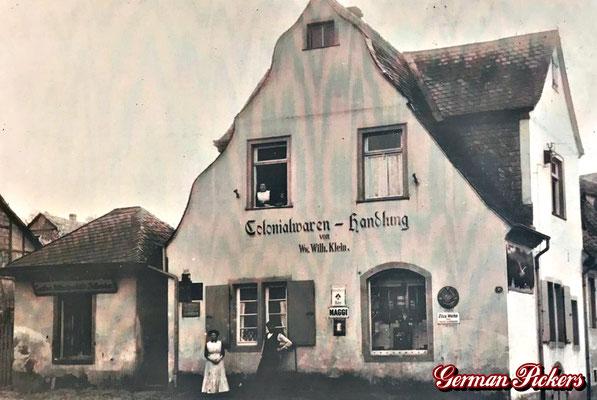 AK / Foto - Colonialwaren-Handlung Wilhelm Klein mit diversen Emailschildern, u.a. Schultheis Bier vom Rhein um 1910