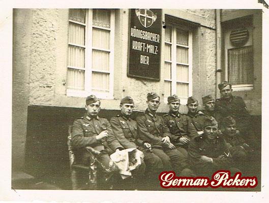 AK / Foto Soldaten im 2. Weltkrieg vor Wirtshaus - Hinterglasschild der Königsbacher Brauerei / Bräu