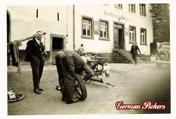 AK / Foto Herren reparieren Motorrad - Im Hintergrung ein Hinterglasschild Nette Bräu Wirtshaus