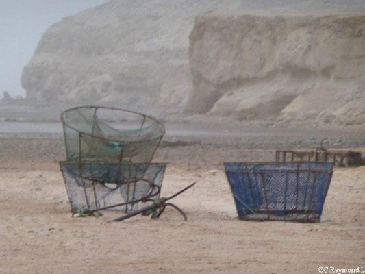 Panier de pêche posé sur la plage avec falaise et océan en fond
