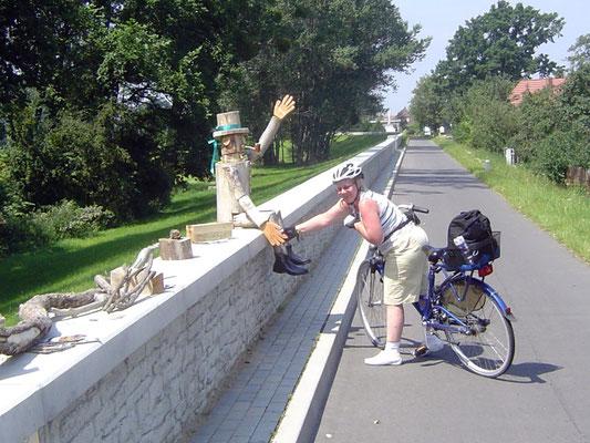 Bei einem Ort mit dem drolligen Namen Iserbegka bringt uns eine lustige Holzfigur am Wegesrand zum Lachen.