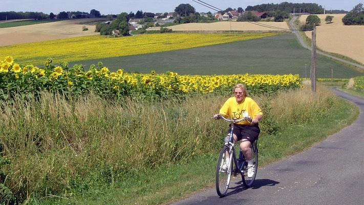 Christine schnauft im Tour-de-France-Trikot einen Berg hinauf.