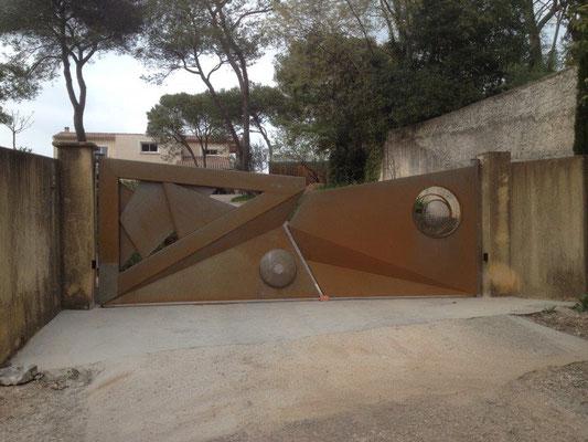 Fabrication d'un portail massif en fer forgé décoration style Oculus industriel à Nimes dans le Gard Finition rouillée nature[