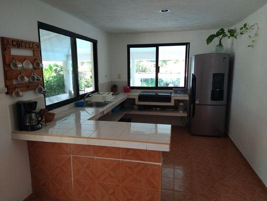 Amplia cocina con vista a la piscina y al mar