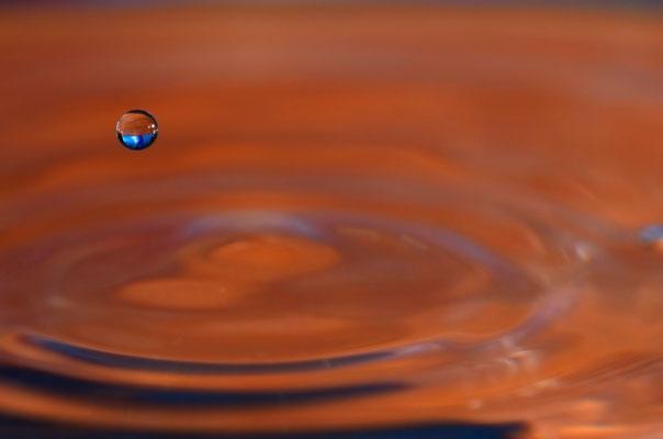 Ein Wassertropfen fällt ins Trinkglas