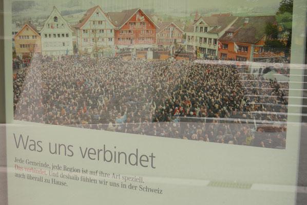 Werbeplakat in einer Appenzeller Bank: Der selbe Platz mit Appenzellern während eines Mehrens...