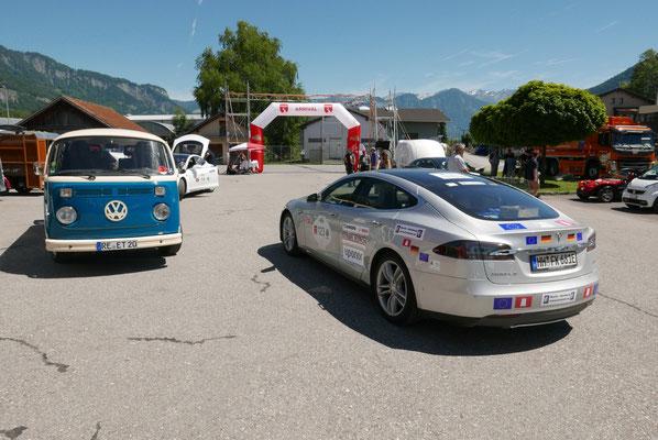 Voll elektrisch in Wildbach - Umgebauter VW-Bus und Tesla vor Hintergrund....