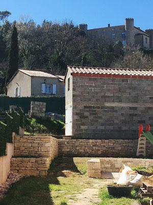 Vue d'ensemble depuis le chemin du Grand Logis. En premier plan à gauche, le mur en pierre sèche et à droite, le muret en parement  de pierres naturelles. Tout au fond, se dresse le château de Mirabeau.