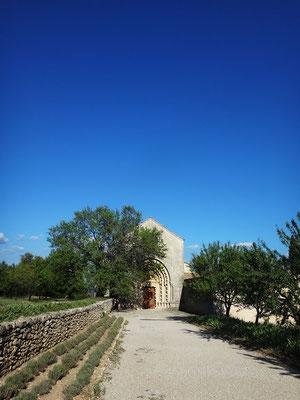 Vue d'ensemble du portail d'entrée et du parvis de l'église N.D. de Ganagobie, qui se trouve à quelques centaines de mètres du mur de clôture. Le ciel, d'un bleu fluide et saturé, est caractéristique de celui du Luberon
