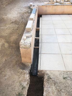 Système d'évacuation des eaux qui permet de drainer les eaux stagnantes sur le dallage de terrasse (caniveaux Nicoll). Une très légère surélévation des pierres de soubassement permet ainsi à l'eau de s'évacuer.