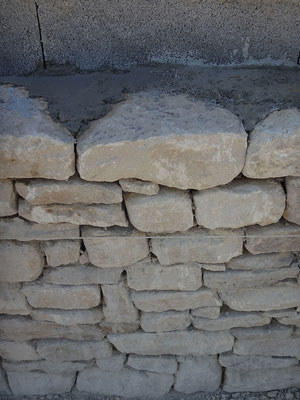 Détail de la répartition du mortier de chaux hydraulique entre la queue de la pierre et le parement du parpaing