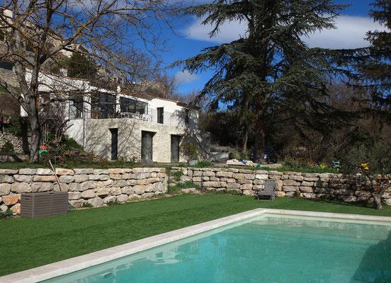 Vue depuis la piscine. Le mur de parement pierres se trouve à l'arrière-plan