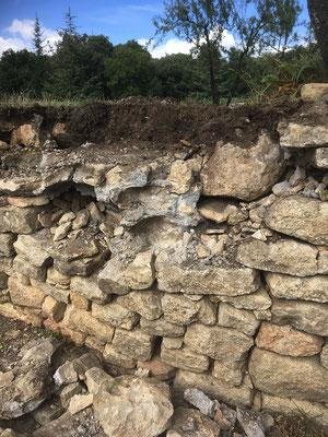 """Aux premières pierres déposées, il s'avère qu'il ne s'agit pas d'un """"vrai"""" mur en pierres sèches. Certaines parties sont maçonnées au mortier de ciment. On se demande ce que fait en haut du mur, le gros bloc calcaire (haut droit image) ?"""
