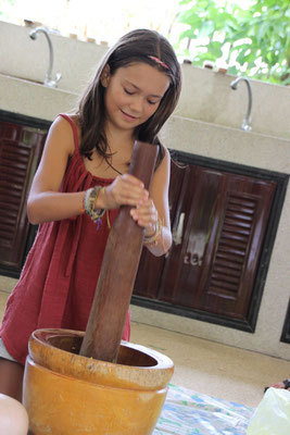 Mara beim Mörsern von Kräutern für Massagestempel, Thailand