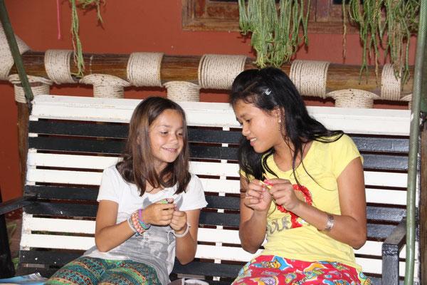 Mara zeigt einem Mädchen wie man Loombänder knüpft, Kambodscha