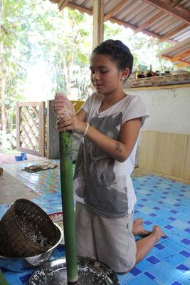 Beim  Kochen, Bambusrohre werden mit Reis gefüllt, Thailand