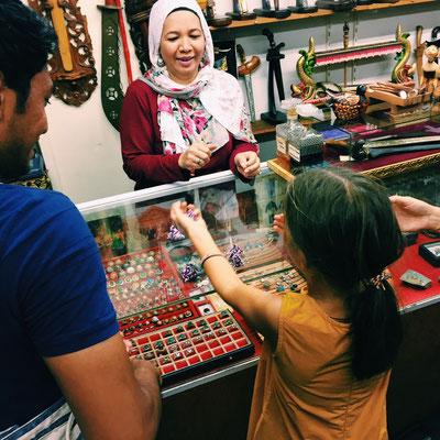 Eine Verkäuferin zeigt ein traditionelles malaiisches Spiel