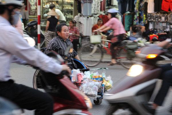 Verkäuferin im Rollstuhl mitten im Hauptverkehr