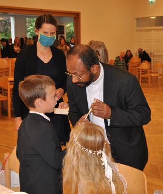 Herr Pfarrer Wilson Abraham überreichte den Kindern gesegnete Kreuze als Andenken an die Erstkommunion.