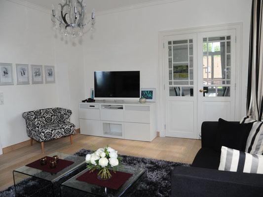 Helles Wohnzimmer mit modernem Fernseher und Stereo-Verstärker; Tür zum Esszimmer.