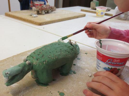 Das Thema des Kurses für Grundschüler: Burgen und Drachen. Hier wird der Ton-Drache gerade mit Engobe bemalt.