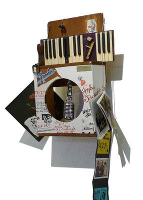 Objektkasten EgoBox 1, selbst gezimmerte, ausgeräumte Lautsprecherbox mit Elfenbeinklaviatur oben, innen: u.a. Shure-Mikro aus den 50ern, außen: Seitenwände mit Originalplakaten tapeziert, H 66 cm (mit Accessoires 110 cm), B 46 cm, T 22 cm; 2016.