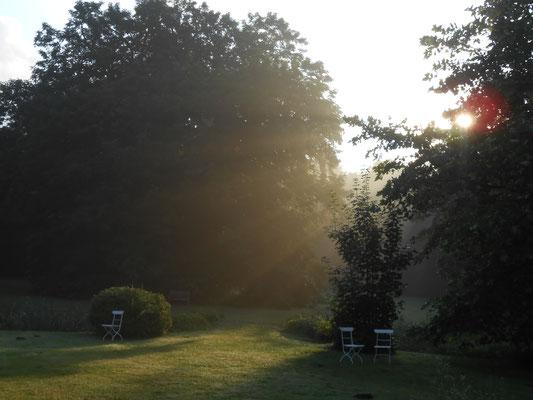Die ersten Strahlen der Morgensonne im Park des Herrenhauses