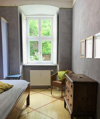 Blick in den Park durch das Fenster des grauen Schlafzimmers